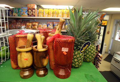 Pilons (for grinding spices), and pineapples at Infante Grocery on Broadway in Lowell, which carries many imported vegetables and brands. (SUN/Julia Malakie)