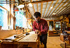 Jason Breen, of Jason Breen Fine & Custom, uses a planer while smoothing out the wood on a standing desk he is working on in his shop.  Kristopher Radder / Reformer Staff