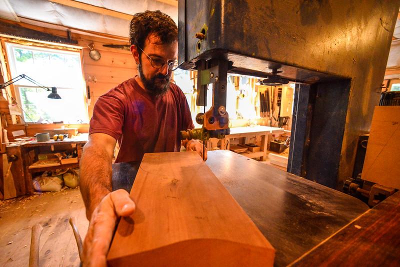 Jason Breen, of Jason Breen Fine & Custom,  uses a bandsaw to cut a circular piece of wood. Kristopher Radder / Reformer Staff