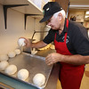 George Bousios of Tyngsboro, founder of Lakeside Pizza & Seafood, is once again owner, buying back the business he sold in 2015. Bousios rolls balls of dough to put in the refrigerator to rise. (SUN/Julia Malakie)