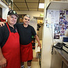 George Bousios of Tyngsboro, left, founder of Lakeside Pizza & Seafood, is once again owner, buying back the business he sold in 2015. At right is employee Flavio Araujo of Lowell. Most of the photos on the wall were there from before Bousios sold the business. He said no one dared take them down. (SUN/Julia Malakie)
