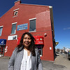 Bora Chiemruom of Boston, who grew up in Lowell, at the building in Cambodian Town on Branch Street, where she'll be opening Kravant Boutique, a dress rental and consignment business. The center and right windows on the second floor are her space. Grand opening is May 12. (SUN/Julia Malakie)