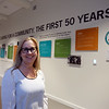 LCHP 50th anniversary year. CEO Sue Levine of Maynard, with timeline of Lowell Community Health Plan history, in the main corridor. (SUN/Julia Malakie)