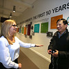 LCHP 50th anniversary year. CEO Sue Levine of Maynard chats with health benefits advisor Mengleang Seak of Lowell, who helps people, including Khmer speakers, enroll in Mass Health and the Health Connector. At rear is a timeline of Lowell Community Health Plan history, in the main corridor. (SUN/Julia Malakie)