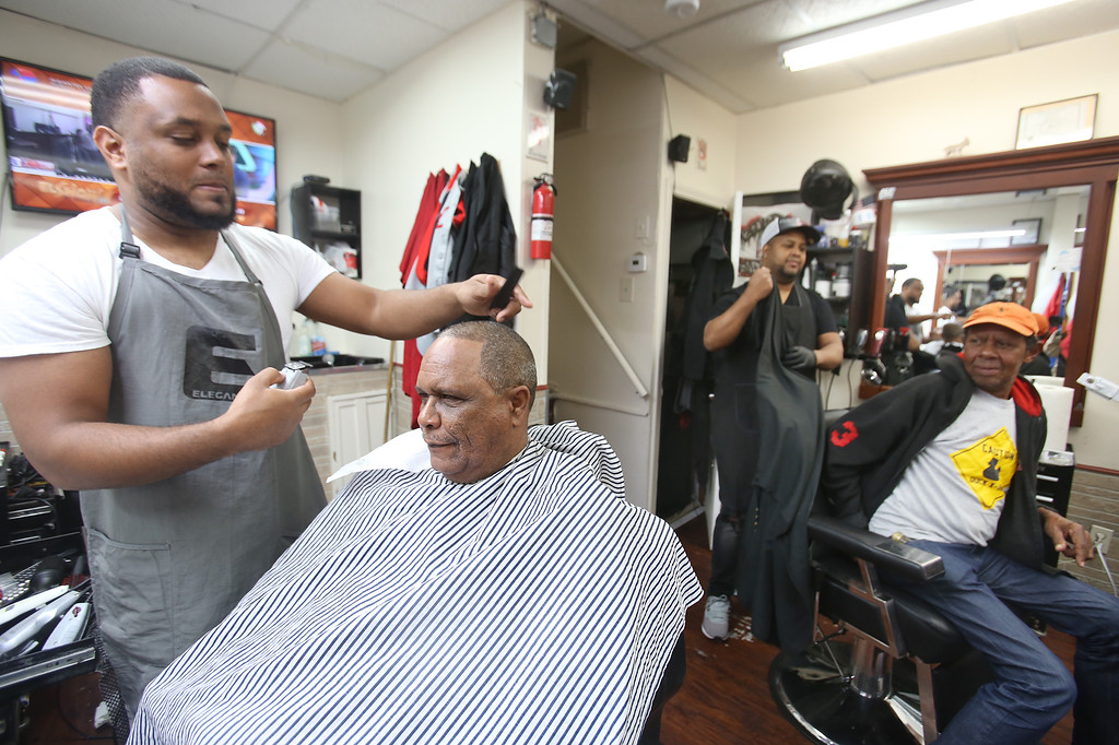 . Los Monstros Barber Shop on Merrimack Street in Lowell. Owner Andres Luciano of Nashua, left, with customer Marco Colon of Lowell. At right are barber Domingo Pichardo of Lowell, just finished with customer Santos Frias de Jesus of Lowell. (SUN/Julia Malakie)