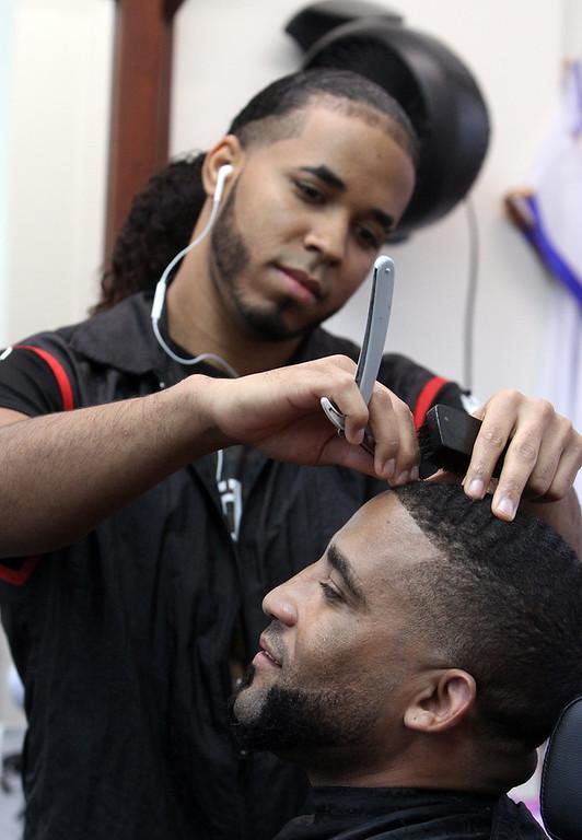 . Los Monstros Barber Shop on Merrimack Street in Lowell. Customer Elvis Ortiz of Lowell gets a haircut from barber Saul Vasquez of Lowell.  (SUN/Julia Malakie)