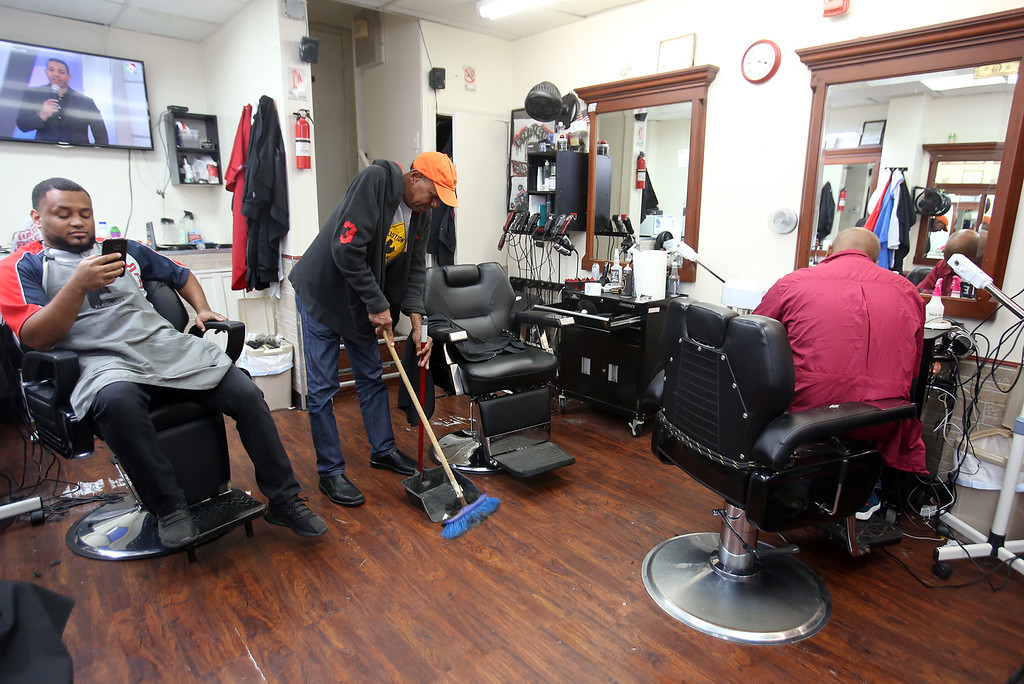 . Los Monstros Barber Shop on Merrimack Street in Lowell. From left, owner Andres Luciano of Nashua during a break between customers, customer Santos Frias de Jesus of Lowell sweeping [they said he sweeps for a couple of dollars], and barber Junior Liriano Sanchez of Lawrence.  (SUN/Julia Malakie)