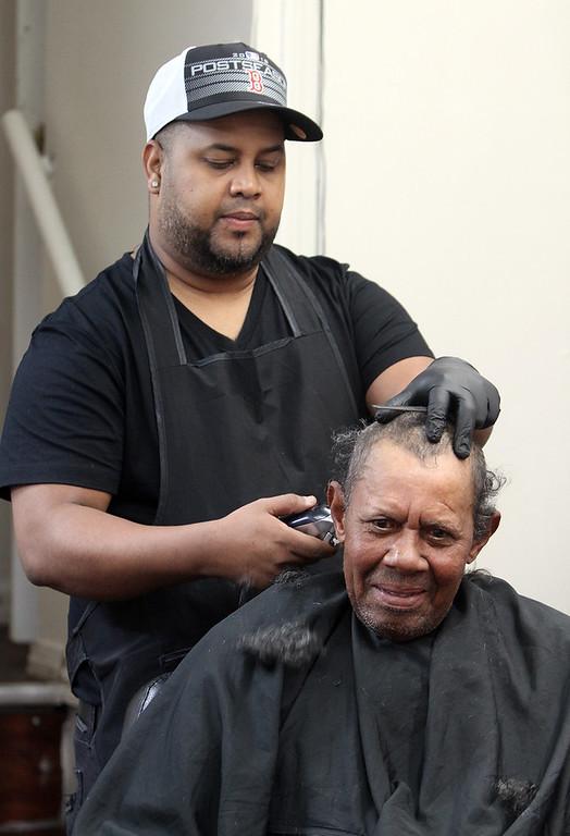 . Los Monstros Barber Shop on Merrimack Street in Lowell.  Barber Domingo Pichardo of Lowell works on customer Santos Frias de Jesus of Lowell.(SUN/Julia Malakie)