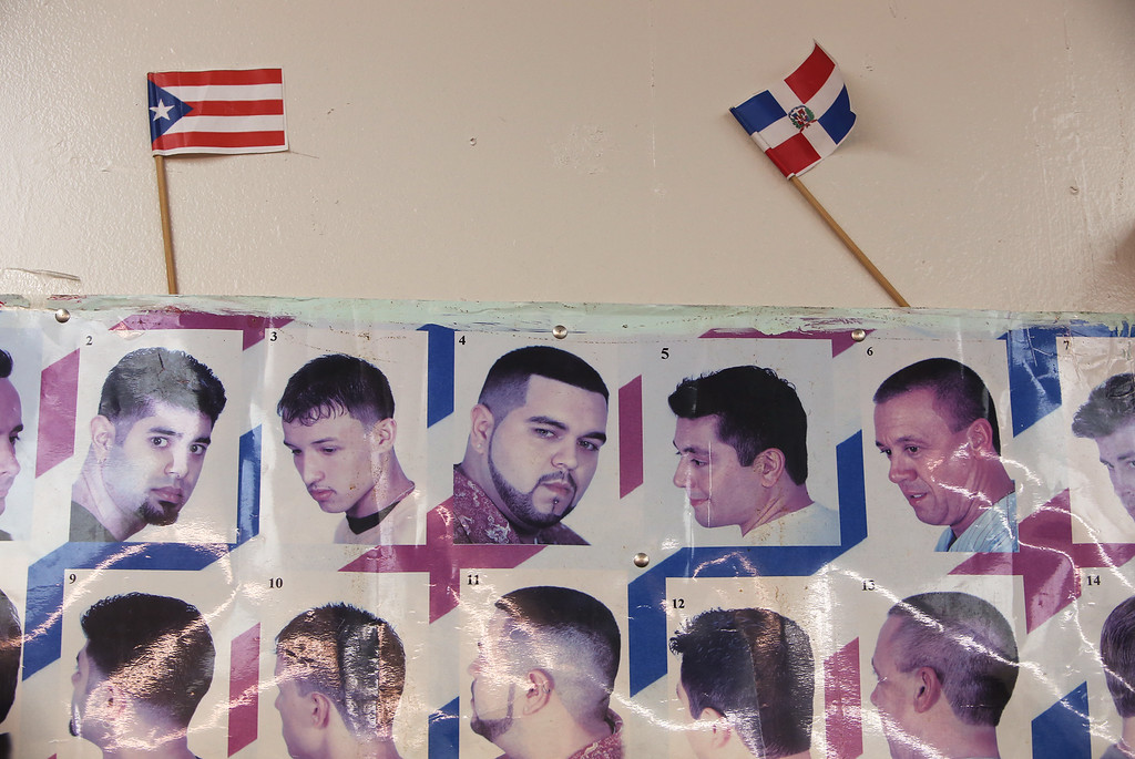 . Puerto Rican and Dominican Republic flags at Los Monstros Barber Shop on Merrimack Street in Lowell.  (SUN/Julia Malakie)
