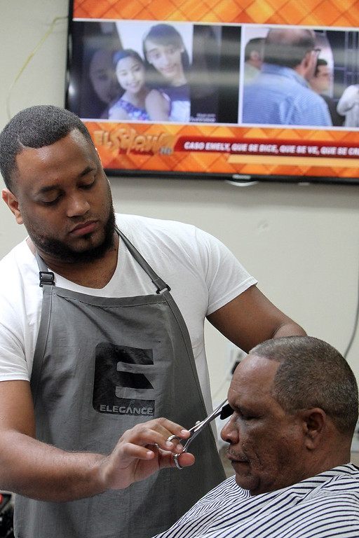 . Los Monstros Barber Shop on Merrimack Street in Lowell. Customer Marco Colon of Lowell gets a trim from owner Andres Luciano. (SUN/Julia Malakie)