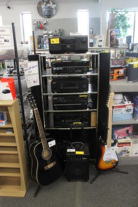 A tower of stereo systems is arranged with two guitars and an amplifier at Main Street Audio Thursday, June 4 at 701 N. Mission St.