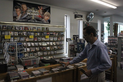 Store Manager Scott Wager adjusts a display of video games and DVDs for sale at Main Street Audio Video Thursday, June 4 at 701 N. Mission St.