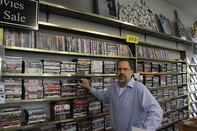 Manager Scott Wager inspects Main Street Audio Video's collection of more than 3,000 DVDs for sale Thursday, June 4 at 701 N. Mission St. Main Street Audio Video recently celebrated 30 years of business in Mt. Pleasant.