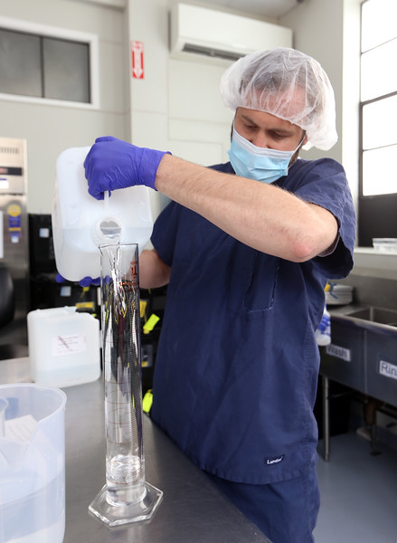 Ben Butterfield of Pepperell, production manager at Compassionate Care medical marijuana facility in Ayer, mixes a batch of hand sanitizer for donation to local hospitals. They use the FDA approved recipe containing ethanol, isopropyl alcohol as a denaturant, hydrogen peroxide and a glycerol/water mix.  (SUN/Julia Malakie)