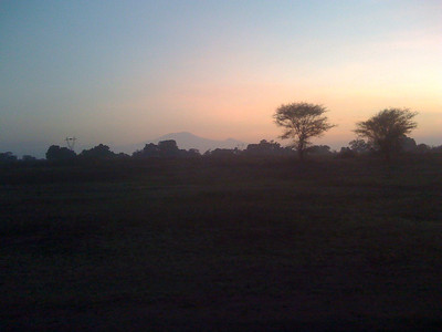the dark mass in the distance is Mount Kilimanjaro