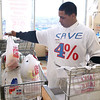 For the remainder of the year, Market Basket is giving shoppers four percent off each grocery order. Wearing a t-shirt, as he bags groceries, to promote the savings is employee Marcos Brown, 24, of Fitchburg. SENTINEL & ENTERPRISE/JOHN LOVE