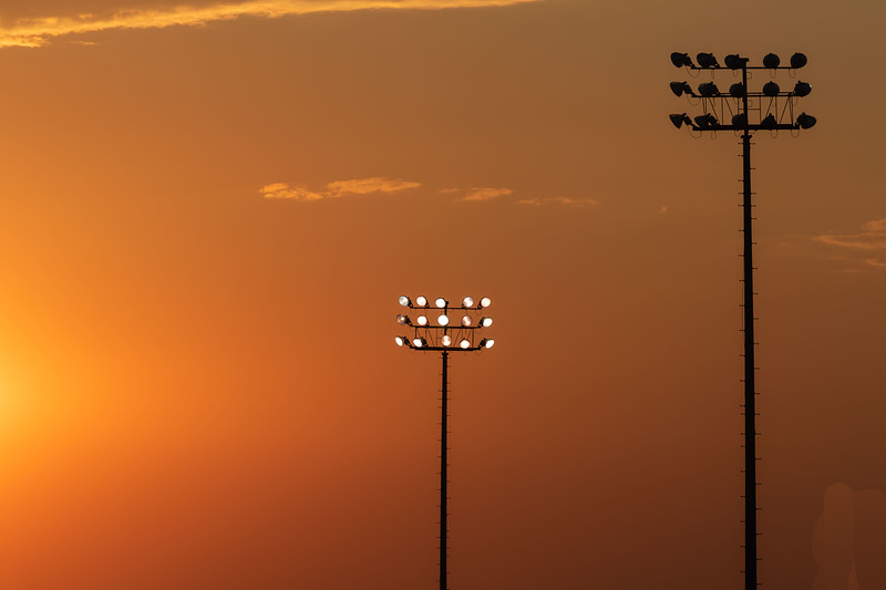 lighting up the soccer field at sunset