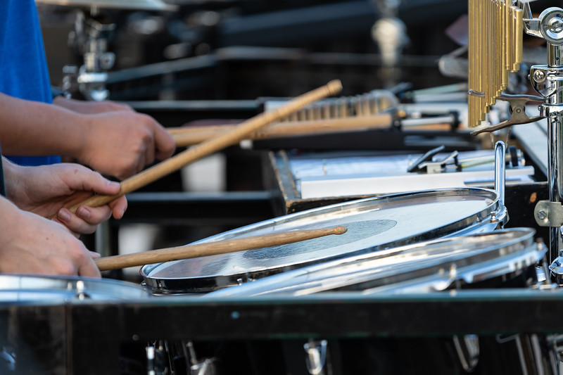 flashing drumsticks of a sideline percussionist at marching band rehearsal