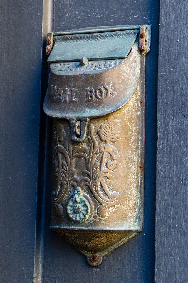 old mail box hanging on an uban building