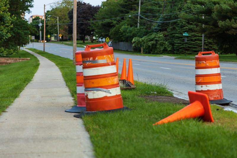 several orange barrels and traffic cones protecting some road repair