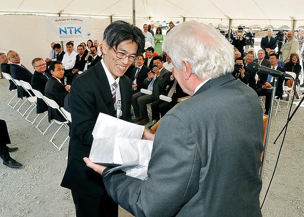 John P. Cleary    The Herald Bulletin<br /> Takayuki Yoshikuni, president of NTK Precision Axle Corp., presents Anderson Mayor Thomas Broderick Jr. a gift during the NTK Precision Axle groundbreaking ceremony Wednesday.