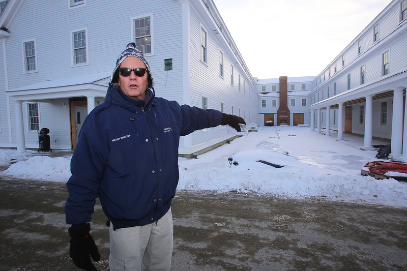 """Warren """"Waddy"""" Francis, general manager of the new Groton Inn, gives a tour around the exterior. This is a new courtyard, with an outdoor fireplace. The Inn is scheduled to open in early May. The previous, historical Groton Inn was destroyed in a 2011 fire. (SUN/Julia Malakie)"""