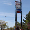 "Paul Lussier of Charlton, installation manager with Philadelphia Sign Company's New England Division, watches from the ground as workers install a new, 21x33ft flexface Target sign at the 120ft high sign tower on Plain Street. The new signs are white on red instead of red on white, and the ""t"" is lower case. (SUN/Julia Malakie)"