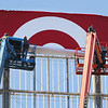 "Workers from Philadelphia Sign Company's New England Division  install a new, 21x33ft flexface Target sign at the 120ft high sign tower on Plain Street. The new signs are white on red instead of red on white, and the ""t"" is lower case. (SUN/Julia Malakie)"