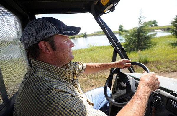 """Geoff Hess rides out to work on the hops field.<br /> The site, combined with the brewery and restaurants, make up a triangle of sustainability for the local craft brewer.<br /> For a video of the farm, go to  <a href=""""http://www.dailycamera.com"""">http://www.dailycamera.com</a>.<br /> Cliff Grassmick / July 8, 2011"""