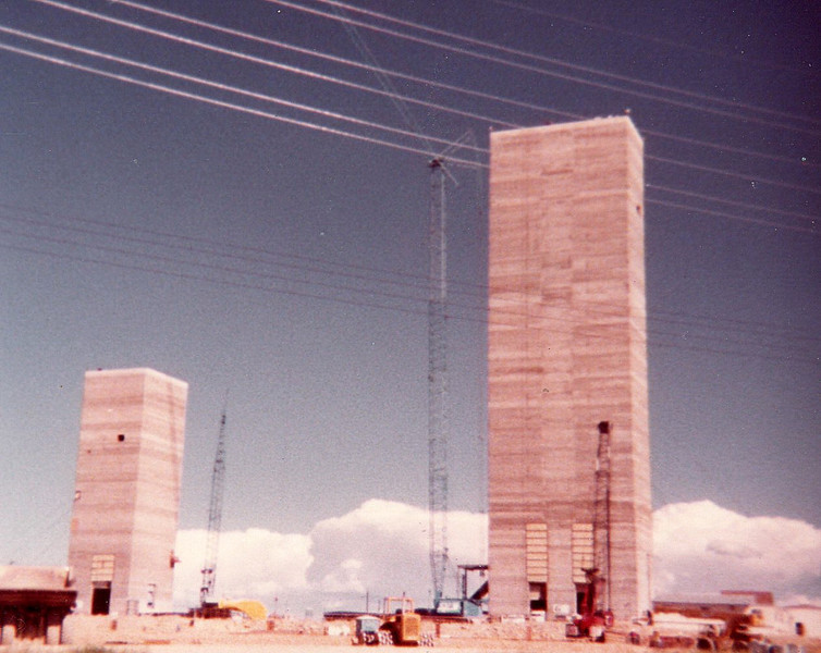 The building on the right is the main shaft head building, it is where the giant muck/man/equipment buckets are lowered into the maim mine shaft. The building is about 700 feet tall. The building on the left is the service building, over the service shaft., about 300 feet tall.