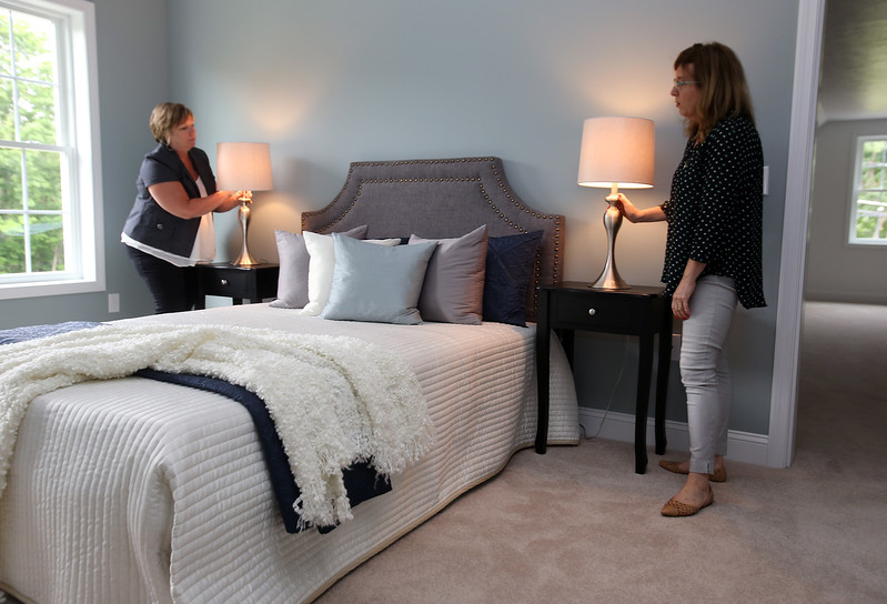 House stagers Jan Poulain, left, and Liz Larson, both of Chelmsford and owners of Perfectly Placed for You LLC, check final touches in the master bedroom of a new construction house on Old Pasture Road in Dracut. (SUN/Julia Malakie)