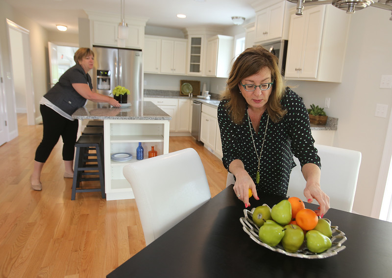 House stagers Liz Larson, right, and Jan Poulain, rear, both of Chelmsford and owners of Perfectly Placed for You LLC, check final touches on a new construction house on Old Pasture Road in Dracut. (SUN/Julia Malakie)
