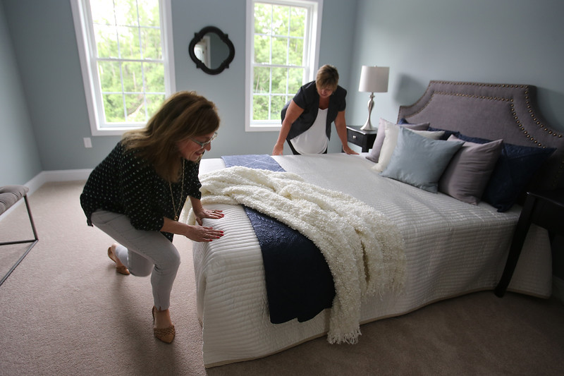 House stagers Liz Larson (polka dots) and Jan Poulain, both of Chelmsford and owners of Perfectly Placed for You LLC, check final touches on a new construction house on Old Pasture Road in Dracut. (SUN/Julia Malakie)
