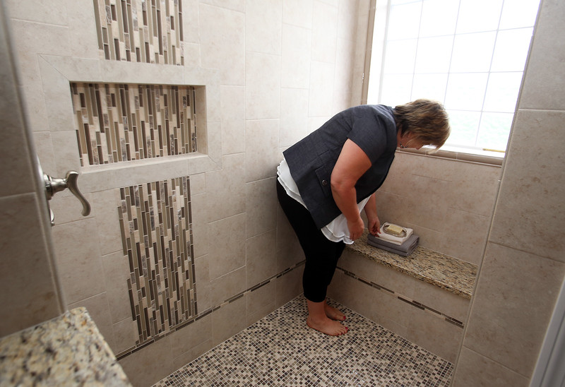 House stagers Liz Larson (polka dots) and Jan Poulain, both of Chelmsford and owners of Perfectly Placed for You LLC, check final touches on a new construction house on Old Pasture Road in Dracut. Jan Poulain took off her shoes to adjust the soap dish in the walk in shower. (SUN/Julia Malakie)