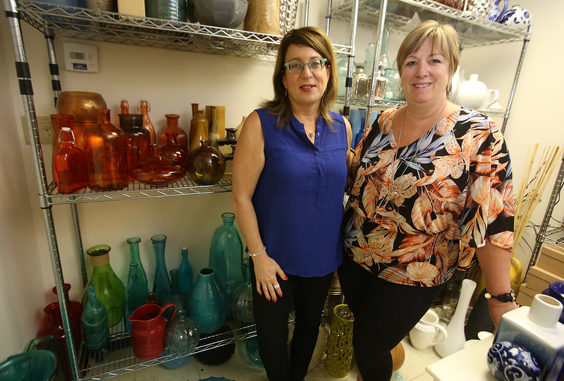 Perfectly Placed for You's warehouse in Billerica, where furniture and other items for house staging are stored. Co-owners Liz Larson, left, and Jan Poulain, both of Chelmsford, with their rainbow selection of vases. (SUN/Julia Malakie)
