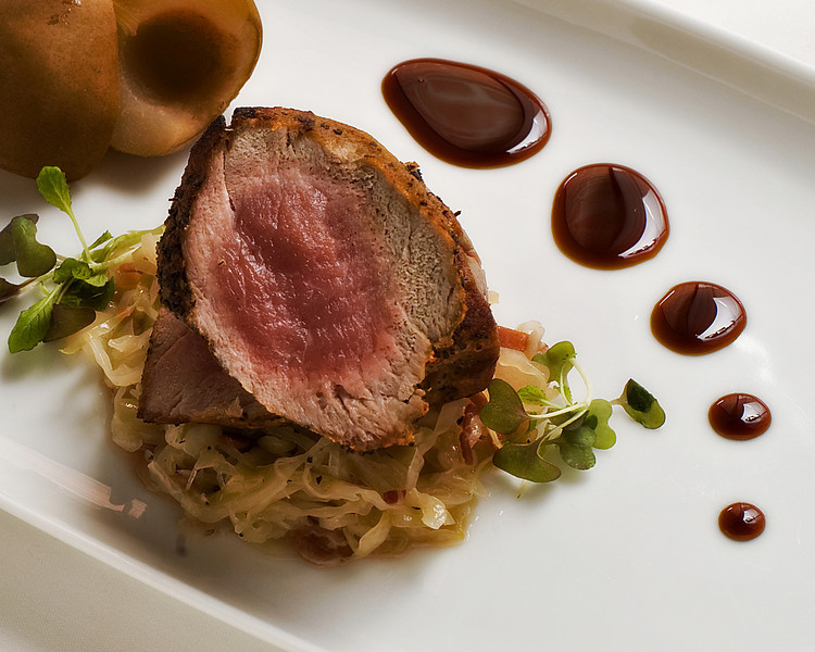 Seared pork tenderloin served with Saba, a spice-poached <br />  Seckel pear  & a kraut of speck & cabbage