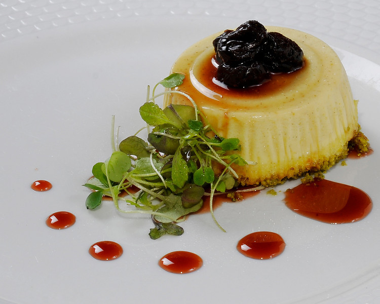 Parmesan cheese flan with a pistachio crust drizzled with  <br /> sour cherry & port wine reduction