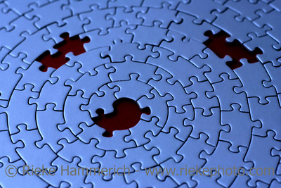 three missing pieces in a blue jigsaw - focus is on the center hole - adobe RGB