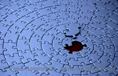 blue jigsaw with the missing piece laying above the space - shallow DOF, focus is on the missing piece - adobe RGB