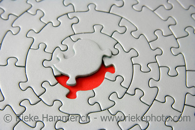 grey jigsaw with the missing piece laying above the red space - pieces fitting together in form of a spiral - adobe RGB