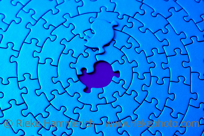 abstract of a blue jigsaw with the missing piece laying above the space - shallow DOF, focus is on the hole - adobe RGB