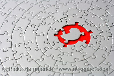 grey jigsaw with space and one of the missing pieces in the red center - pieces fitting together in form of a spiral - adobe RGB