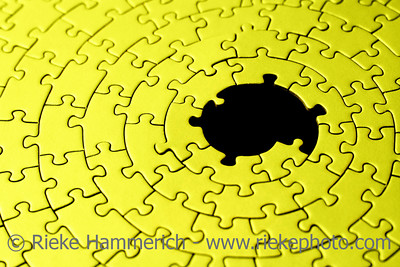 abstract of a yellow jigsaw with missing pieces in the black center - shallow DOF, focus is on the big hole - adobe RGB