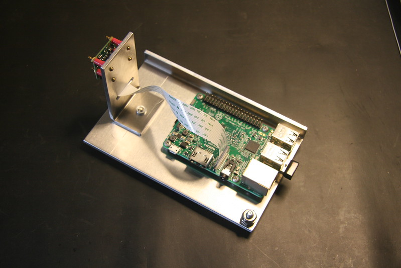 "An 1/8"" aluminum chassis to hold the Raspberry pi 3 model B board with camera module V2.  It's a nominal 3"" x 5"" footprint.  Screw in lower right is for a frame ground."