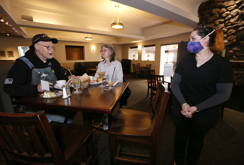 Slattery's Bar & Grill in Fitchburg. Business is coming back after a downturn due to the Covid-19 pandemic. Server Jennifer DeLuca of Fitchburg, right, checks on regular customers Graham Clark and his wife Elaine Clark of Gardner, having a late lunch. JULIA MALAKIE/LOWELLSUN