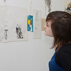 SENTINEL&ENTERPRISE/Ashley Green -- <br /> Casey Taylor, of Fitchburg, a volunteer at the gallery, admires artwork during the Revival Gallery's one year anniversary show on Friday evening. Revival Gallery is located at 713 Main Street in Fitchburg.