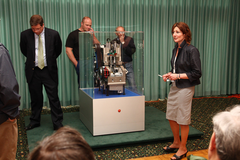 Cindy Fioretti, daughter of Carmelo Scuderi, explaining the Scuderi engine to a group of inquiring onlookers, while Bill Wrinn,  Scuderi Group Director of Marketing/Communications, contemplates his next discussion point.