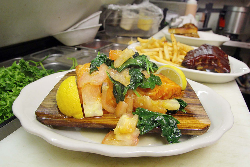 Sharky's restaurant will be participating in this years Taste of Leominster at the end of the month. They where serving up a cedar plank salmon florentine with two sides on Monday at their location on Lancaster Street. Behind this dish in the kitchen is a half rack of ribs with fries. SENTINEL & ENTERPRISE/JOHN LOVE