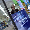 KRISTOPHER RADDER — BRATTLEBORO REFORMER<br /> Pat Fowler, owner of Village Square Booksellers, in Bellows Falls, hangs a poster for Small Business Saturday in her store's window on Monday, Nov. 19, 2018.