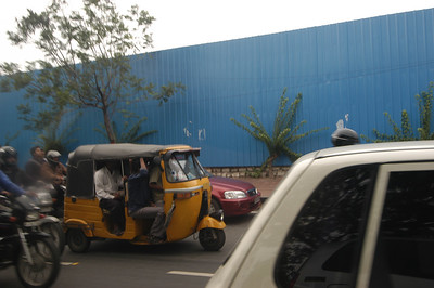 It is sorta hard to see but there are six people in that rickshaw!